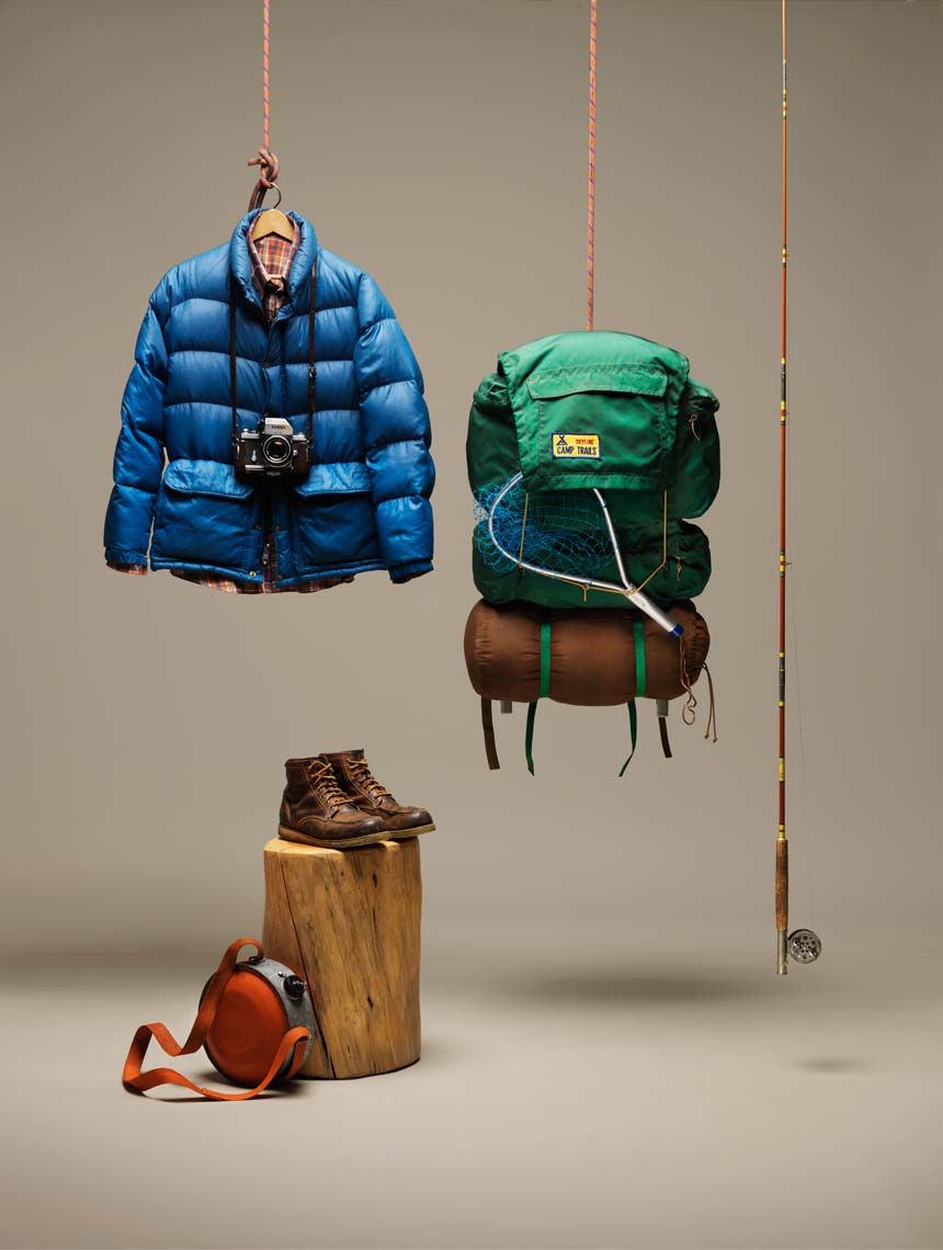 backpacking gear fishing pole and puffy coat on a tan background