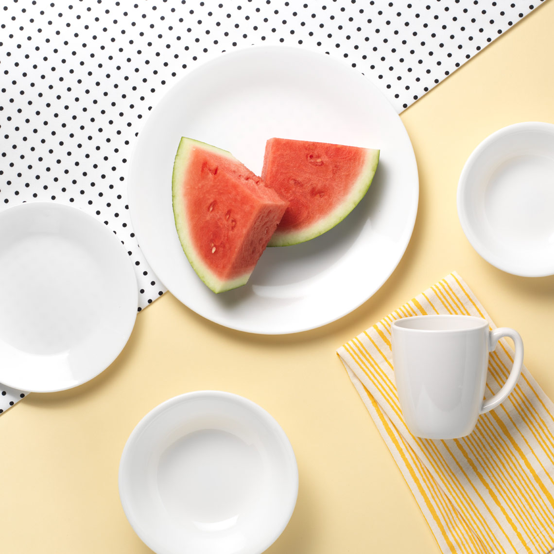 plates on a yellow black and white polka dot table with watermelon