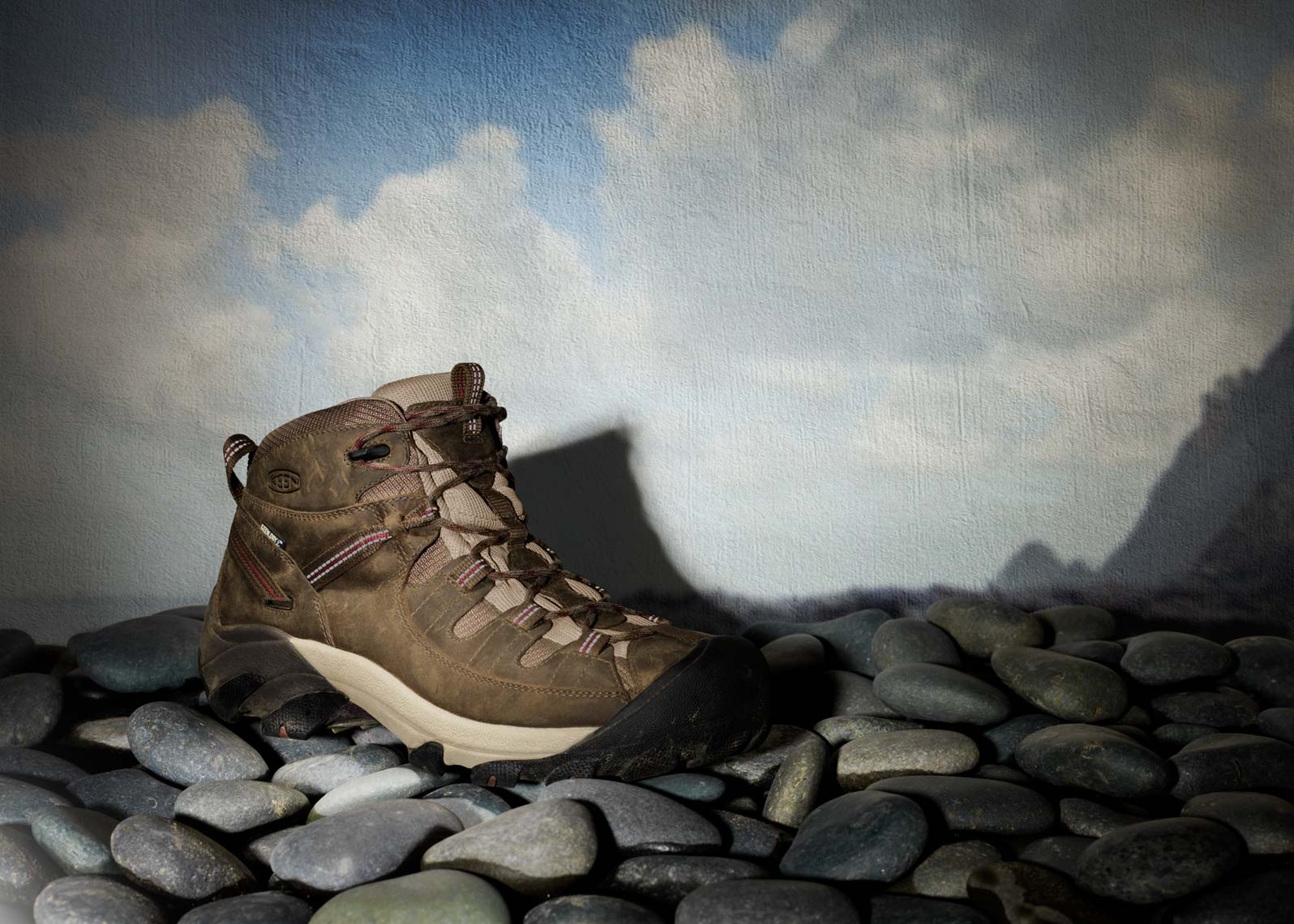 keen hiking boot on a rocky shoreline blue brown