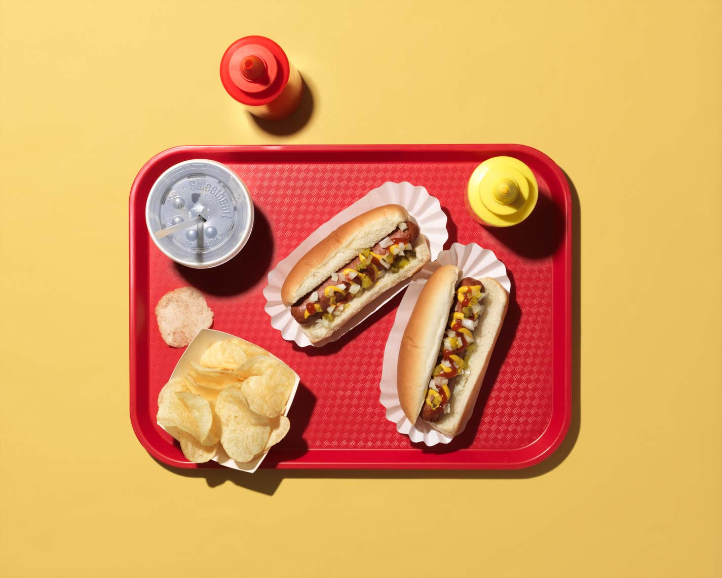 hot dog pop and chips on a red tray