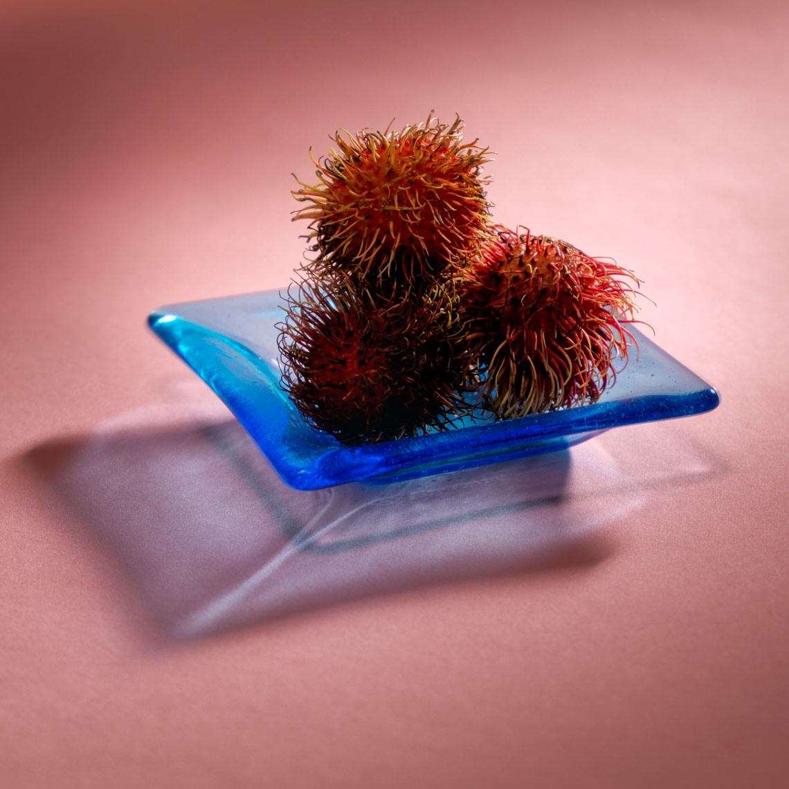 rambutan fruit on a blue glass plate