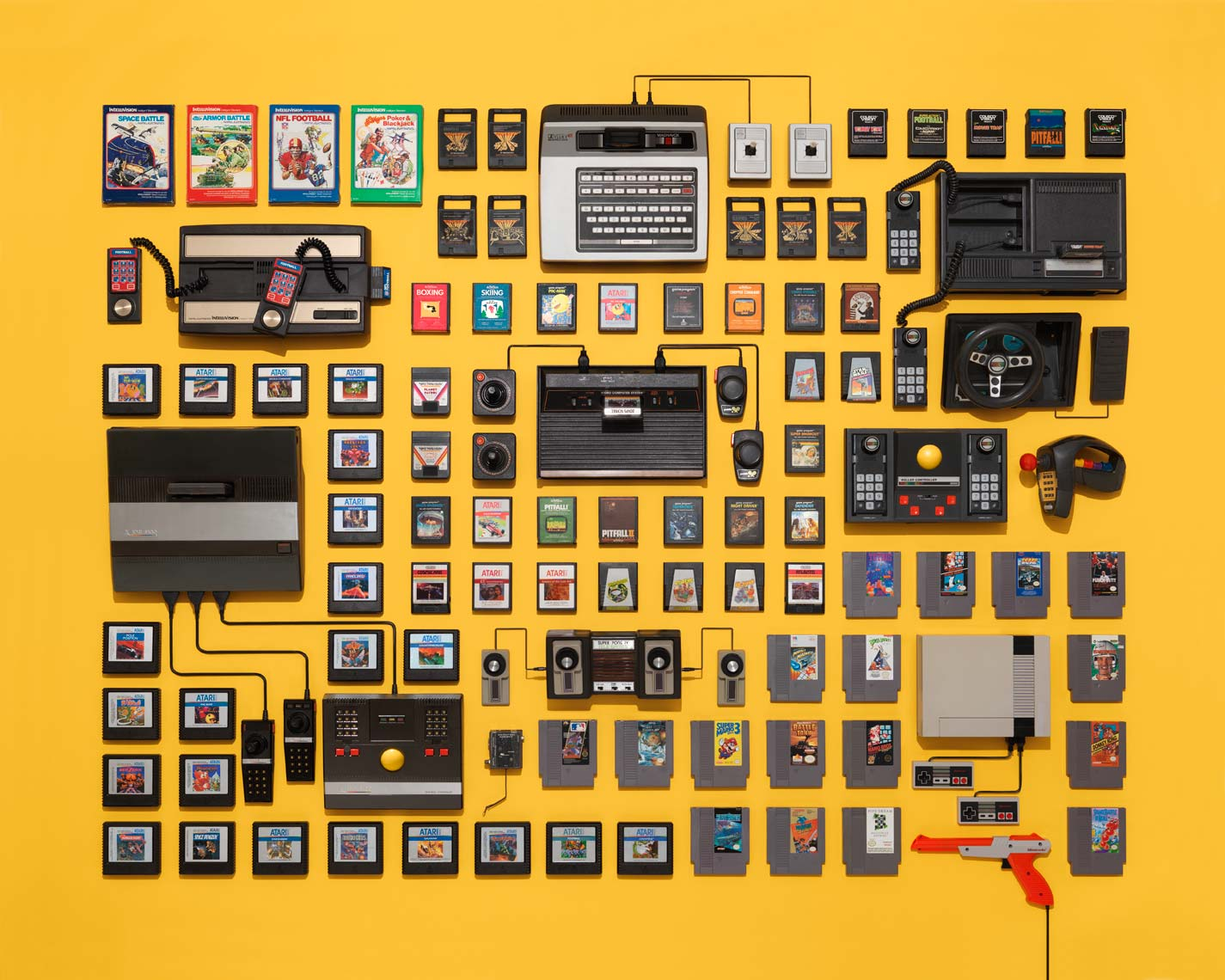vintage video game consoles and cartridges on a yellow background