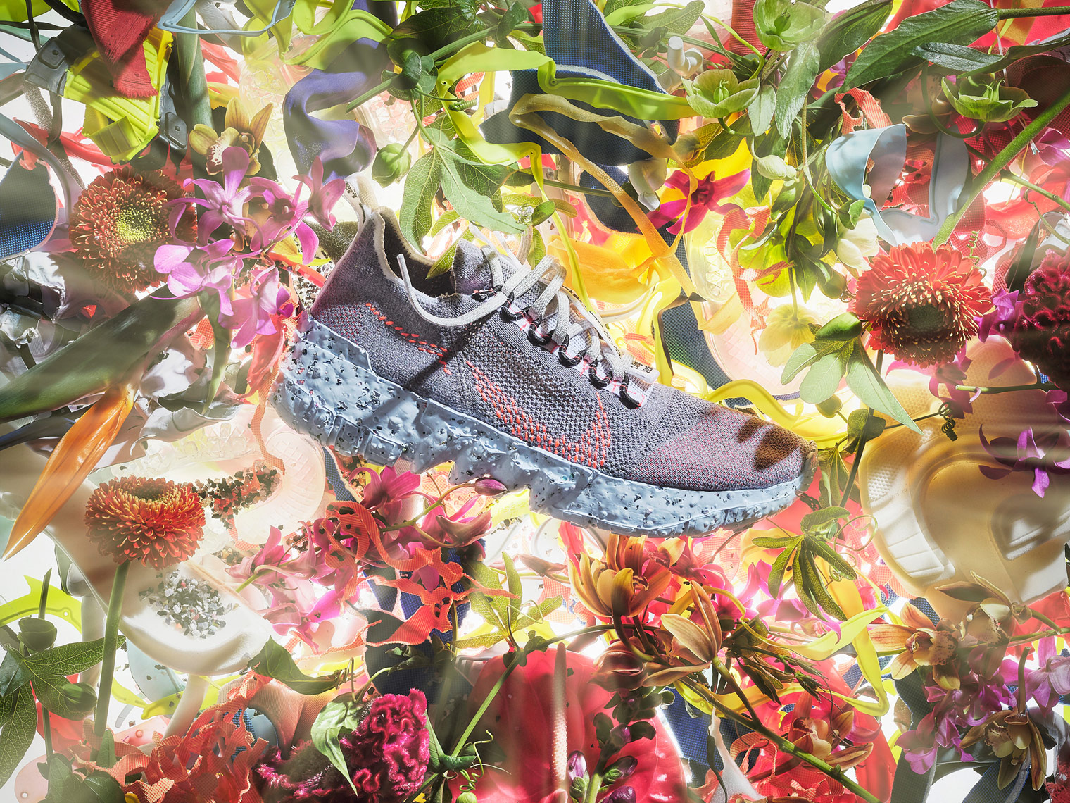 nike space hippie trainer on a bed of flowers with light rays