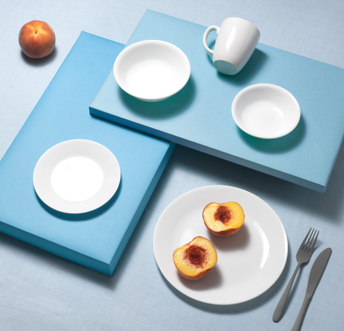 correlle plates and mug on blue with peaches