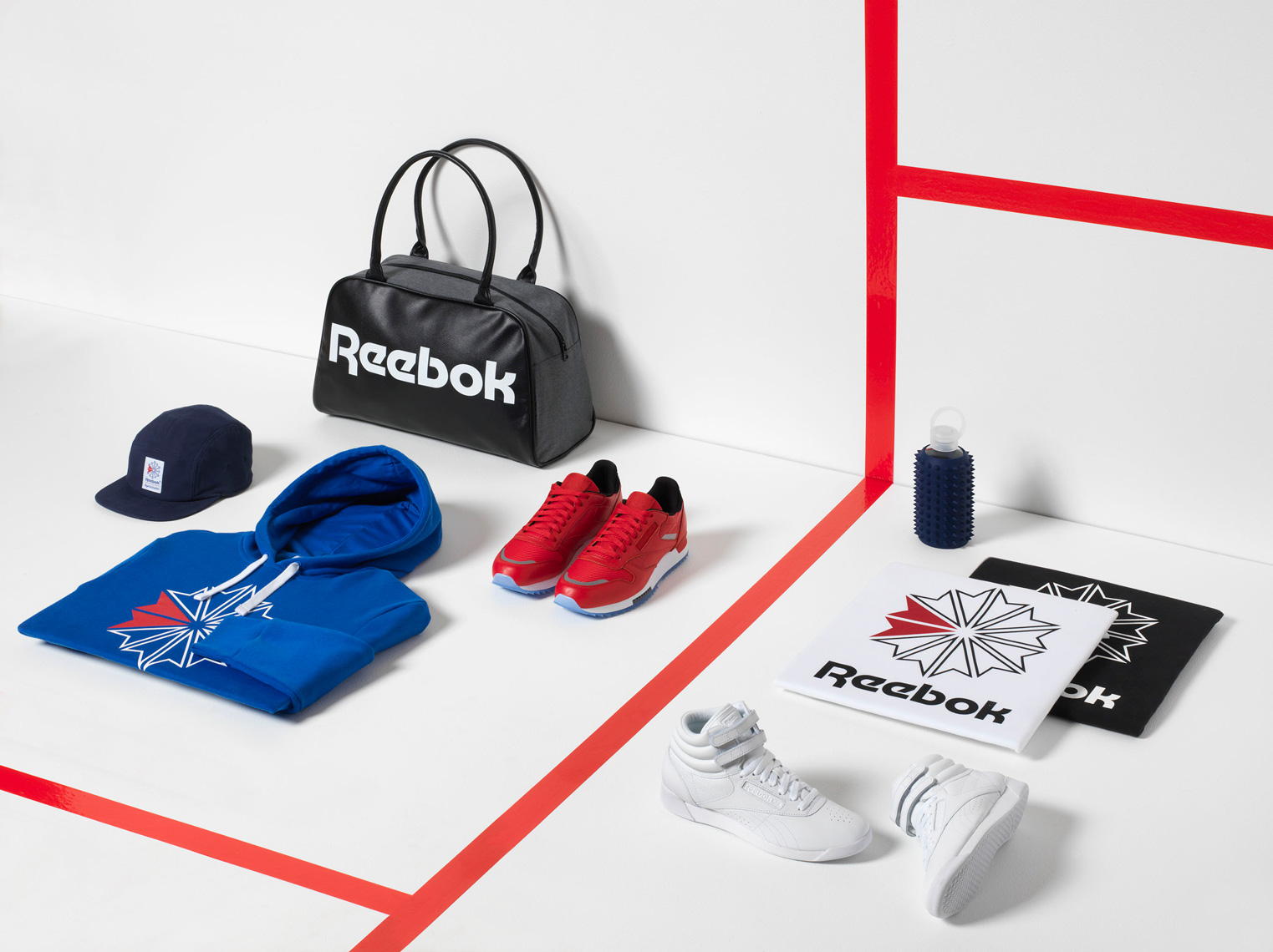 mens reebok sportswear on a white court with red stripe